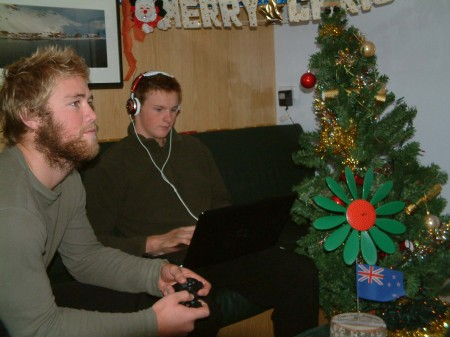 Josh checking out the X-box while Nick writes an e-mail home on Christmas day.